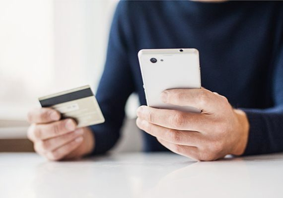 Male hands holding credit card and using smart phone. Online sho
